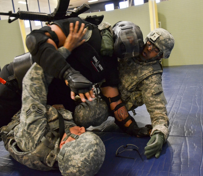 Senior Airman Savas Rivera, 612th Support Squadron, along with Capt. Carlos Semidey,  1st Battlefield Coordination Detachment, wrestle with a non compliant combative during the Modern Army Combatives Program (MACP) Basic Combatives Course Level 1 at Davis-Monthan Air Force Base, Ariz., Jan. 16, 2014. The 40-hour course focuses on the three phases of basic fighting strategy; close the distance, gain the dominate position, and how to finish the fight. (U.S. Air Force photo by Staff Sgt. Adam Grant/Released)