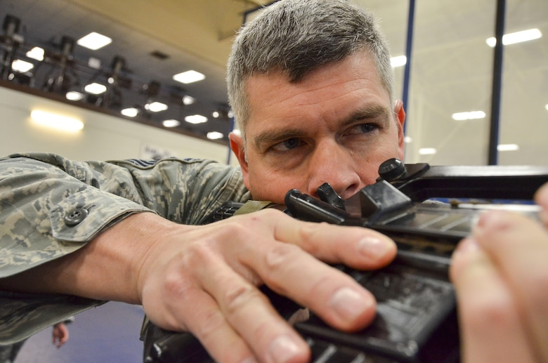 Senior Master Sgt. Kevin Wendt, 612th Support Squadron, practices looking down the sight of his weapon before going through the room clearing portion of the Modern Army Combatives Program (MACP) Basic Combatives Course Level 1 at Davis-Monthan Air Force Base, Ariz., Jan. 16, 2014.The 40- hour course focuses on the three phases of basic fighting strategy; close the distance, gain the dominate position, and how to finish the fight. (U.S. Air Force photo by Staff Sgt. Adam Grant/Released)