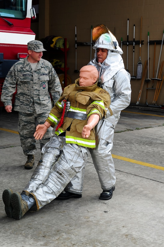 Kerin Barrera, a member of a Honduran fire brigade, drags a 175-pound dummey 100 feet during a fire muster hosted by the firefighters of Joint Task Force-Bravo's 612th Air Base Squadron, Jan. 16, 2014.  Thirty members of local Honduran fire brigades and volunteer fire departments participated in the fire muster, which served to bring U.S. and Honduran firefighters together to build camaraderie, engage in training, and take part in friendly competition.  (Photo by Martin Chahin)