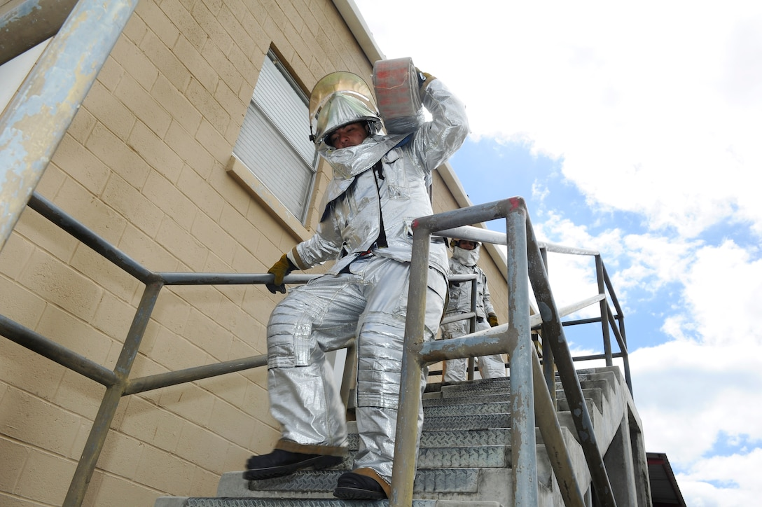 Alexis Murillo, a member of a Honduran fire brigade, carries a 45-pound fire hose down a flight of stairs during a fire muster hosted by the firefighters of Joint Task Force-Bravo's 612th Air Base Squadron, Jan. 16, 2014.  Thirty members of local Honduran fire brigades and volunteer fire departments participated in the fire muster, which served to bring U.S. and Honduran firefighters together to build camaraderie, engage in training, and take part in friendly competition.  (Photo by Martin Chahin)