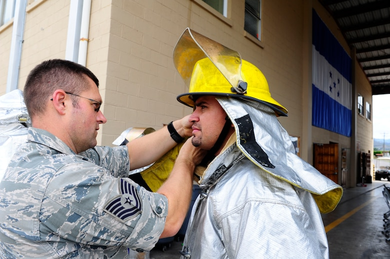 U.S. Air Force Tech. Sgt. Clive Chipman, Soto Cano Fire Department Assistant Chief of Operations, assists Gustavo Triminio, a member of a Honduran fire brigade, in donning firefighting equipment during a fire muster hosted by the firefighters of Joint Task Force-Bravo's 612th Air Base Squadron, Jan. 16, 2014.  Thirty members of local Honduran fire brigades and volunteer fire departments participated in the fire muster, which served to bring U.S. and Honduran firefighters together to build camaraderie, engage in training, and take part in friendly competition.  (Photo by Martin Chahin)