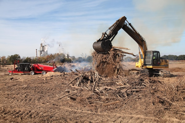 A worker piles debris from Dredge Material Containment Area 1N into a pit of fire. The 130-acre dredge disposal area, located on Onslow Island in Georgia, is being reactivated by the U.S. Army Corps of Engineers, Savannah District through a process called air curtain burning.