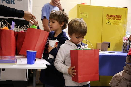 Two boys receive their gift bags at 1st Air Naval Gunfire Liaison Company's town hall meeting aboard Camp Pendleton, Calif., Jan. 15. The meeting allowed families to ask questions and get a better sense of ANGLICO's structure and purpose.