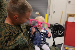 Capt. Benjamin Reading and his daughter show off their new sunglasses at 1st Air Naval gunfire Liaison Company's town hall meeting aboard Camp Pendleton, Calif., Jan 15. The meeting allowed families to ask questions and get a better sense of ANGLICO's structure and purpose.