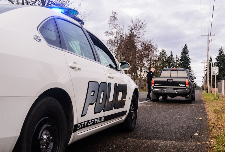 Master Sgt. Phil Ryan, 62nd Airlift Wing Inspector General complaint resolution superintendent, also a reserve police officer at the Yelm Police Department, collects a driver's information following a traffic stop, Dec. 14, 2013, in Yelm, Wash. As a sworn peace officer, Ryan volunteers his free time with police department. (U.S. Air Force photo/Tech. Sgt. Sean Tobin)