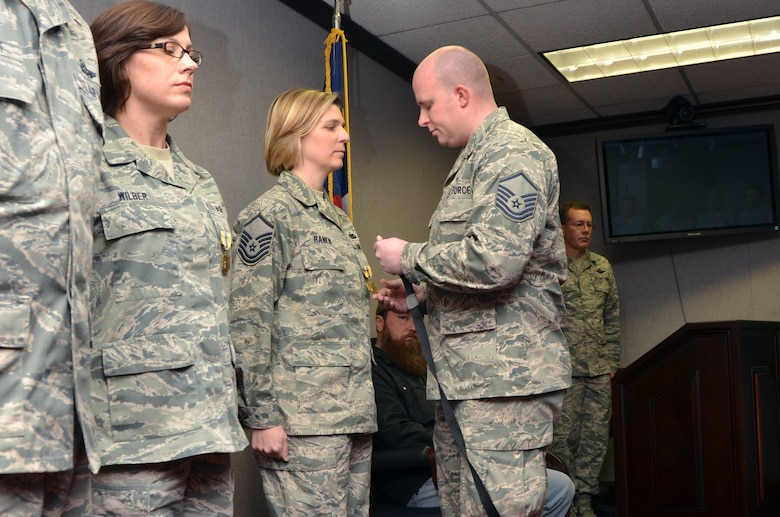 U.S. Air Force Master Sgt. Tracie Rankin, 1st Sergeant for the 145th Mission Support Group, receives Air Force Commendation Medal, as she is recognized for her contributions as Family Liaison Officer to MAFFS 7 survivor, Master Sgt. Josh Marlowe, loadmaster for the 156th Airlift Squadron.  Marlowe pins medal onto Rankin during an emotional ceremony held at the North Carolina Air National Guard base, Charlotte-Douglas Intl. airport, January 11, 2014. (Air National Guard photo by Master Sgt. Patricia F. Moran, 145th Public Affairs/Released)