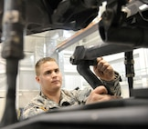U.S. Army Spc. Todd Gann, 1-135th Attack/Reconnaissance Battalion aircraft maintainer, checks for axial play within the bushing of an AH-64 Apache at Whiteman Air Force Base, Mo., Jan. 9, 2014. This inspection ensures that aircraft maintains its structural integrity while in flight. (U.S. Air Force photo by Airman 1st Class Keenan Berry/Released)