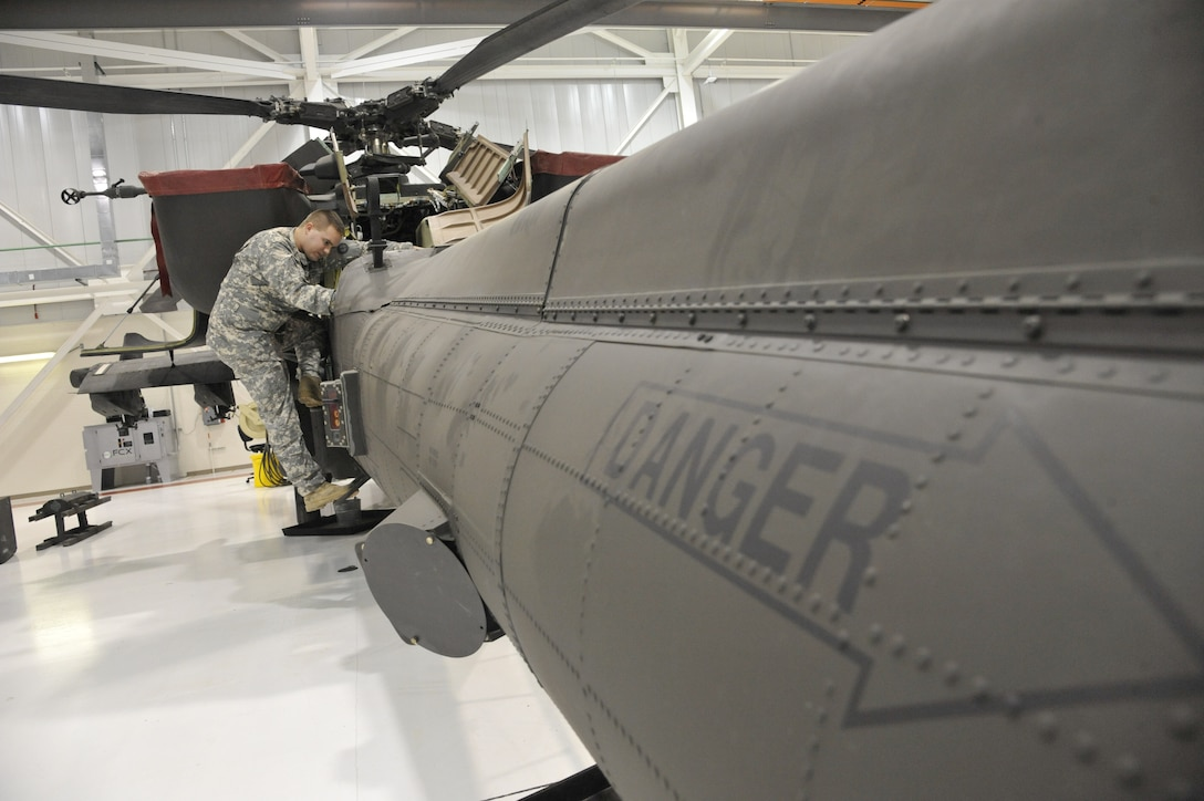 U.S. Army Spc. Todd Gann, 1-135th Attack/Reconnaissance Battalion aircraft maintainer, checks bearings for axial movement within the tail of an AH-64