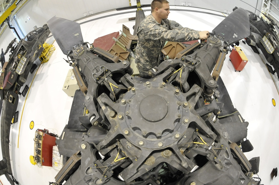 U.S. Army Spc. Todd Gann, 1-135th Attack/Reconnaissance Battalion aircraft maintainer, inspects the main rotor head of an AH-64 Apache at Whiteman Air Force Base, Mo., Jan. 9, 2014. Soldiers perform this inspection annually to ensure there are no signs of corrosion developing, which could cause malfunctions. (U.S. Air Force photo by Airman 1st Class Keenan Berry/Released)