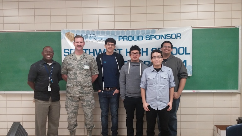 Lt. Col. Jim Burleigh, Cyber Mission Forces Planner for 24th Air Force, met with Mr. Arthur Celestin (left), coach of the Southwest High School CyberPatriot team, and team members from Southwest High School in San Antonio Jan. 15.  Southwest High School was one of 50 teams nationally to make the CyberPatriot semi finals.  (U.S. Air Force photo/2nd Lt. Meredith Hein)