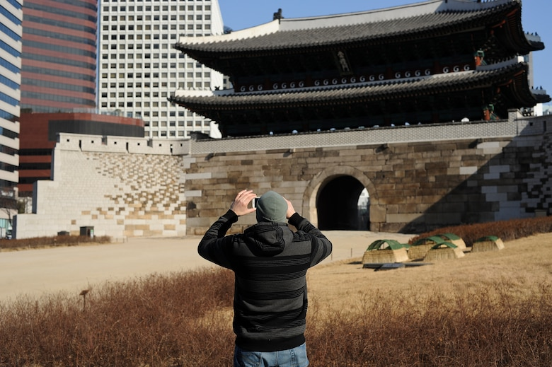 A traveler takes a picture of the Namdaemun Sungnyemun Gate Jan. 18, 2014, in Seoul, Republic of Korea. The Sungnyemun Gate is an ancient structure originally built around 1395 and stands as one of the eight gates of the Fortress Wall of Seoul.(U.S. Air Force photo by Staff Sgt. Jake Barreiro)