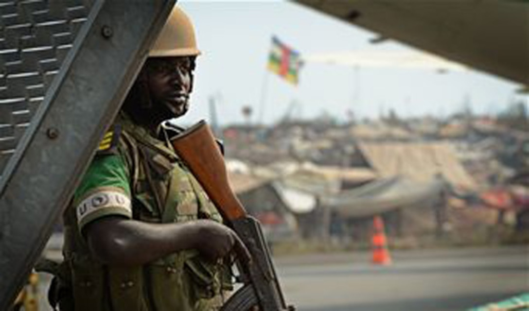 A Rwandan soldier stands guard Jan. 19, 2014, at an airfield in the Central African Republic with a refugee camp full of displaced citizens. U.S. forces will transport a total number of 850 Rwandan soldiers and more than 1,000 tons of equipment into the Central African Republic to aid French and African Union operations against militants during this three week-long operation. (U.S. Air Force photo/Staff Sgt. Ryan Crane)