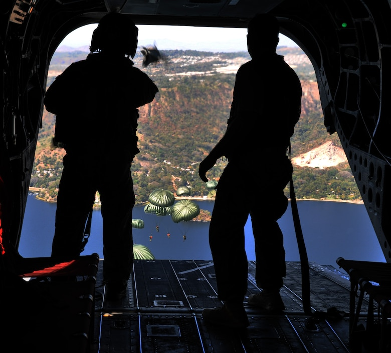 A crewchief and jumpmaster watch as U.S. Special Forces and El Salvadoran military members maneuver under canopy after jumping from the ramp of a CH-47 Chinook helicopter at an altitude of 1,250 feet during a joint airborne operations training exercise conducted by U.S. Special Forces and El Salvadoran servicemembers over Lake Ilopango, El Salvador, Jan. 21, 2014.  U.S. Special Forces from the 7th Special Forces Group (Airborne) conducted the training exercise alongside members of the El Salvadoran military.  The joint-training, overwater static jump allowed members from both nations to maintain currency while strengthening the relationship between the U.S. and El Salvadoran forces.  Joint Task Force-Bravo's 1-228th Aviation Regiment provided aerial support for the exercise, flying each chalk of jumpers from the Ilopango International Airport to the drop zone over Lake Ilopango.  (U.S. Air Force photo by Capt. Zach Anderson)