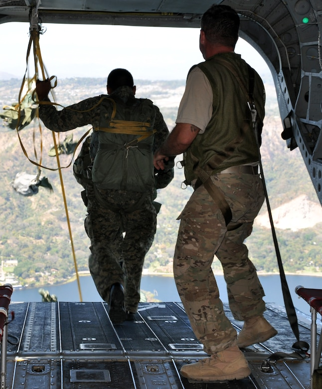 A jumpmaster looks on as a member of the El Salvadoran military jumps from the ramp of a CH-47 Chinook helicopter during a joint airborne operations training exercise conducted by U.S. Special Forces and El Salvadoran servicemembers over Lake Ilopango, El Salvador, Jan. 21, 2014.  U.S. Special Forces from the 7th Special Forces Group (Airborne) conducted the training exercise alongside members of the El Salvadoran military.  The joint-training, overwater static jump allowed members from both nations to maintain currency while strengthening the relationship between the U.S. and El Salvadoran forces.  Joint Task Force-Bravo's 1-228th Aviation Regiment provided aerial support for the exercise, flying each chalk of jumpers from the Ilopango International Airport to the drop zone over Lake Ilopango.  (U.S. Air Force photo by Capt. Zach Anderson)