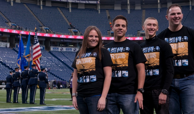 Airmen 1st Class Audrey Mueller, left, Joe Fonseca, Tanner Johnson, and Brian Willis, 133rd Security Force Squadron, pose for a photograph at the Mall of America Field in Minneapolis, Minn., Dec. 1, 2013. The Airmen are going to take part in an oath of enlistment ceremony before the Minnesota Vikings verses the Chicago Bears game.