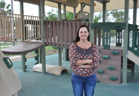 "Tanya Trujillo, 45th Force Support Squadron family care coordinator, poses in front of the Child Development Center at Patrick Air Force Base, Fla. Dec. 13, 2013. ""Being the family care coordinator is an incredibly rewarding experience,"" said Trujillo. ""You get to build a relationship with the children and see them grow and succeed."""