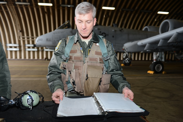 Maj. (Dr.) Jeffrey Woolford, Air Force Institute of Technology student, goes through maintenance forms before taking his second fini-flight in the A-10 Thunderbolt II at Spangdahlem Air Base, Germany, Jan. 17, 2013. At this time, Woolford was an A-10 pilot with the 81st Fighter Squadron at Spangdahlem. Woolford took his first fini-flight when he transitioned into active duty from the Air National Guard to become a pilot-physician.  A fini-flight is a tradition that celebrates a pilot's final flight in an aircraft. He took two because upon re-entering active duty there was no guarantee that he would return to flight. (U.S. Air Force photo by Staff Sgt. Natasha Stannard)