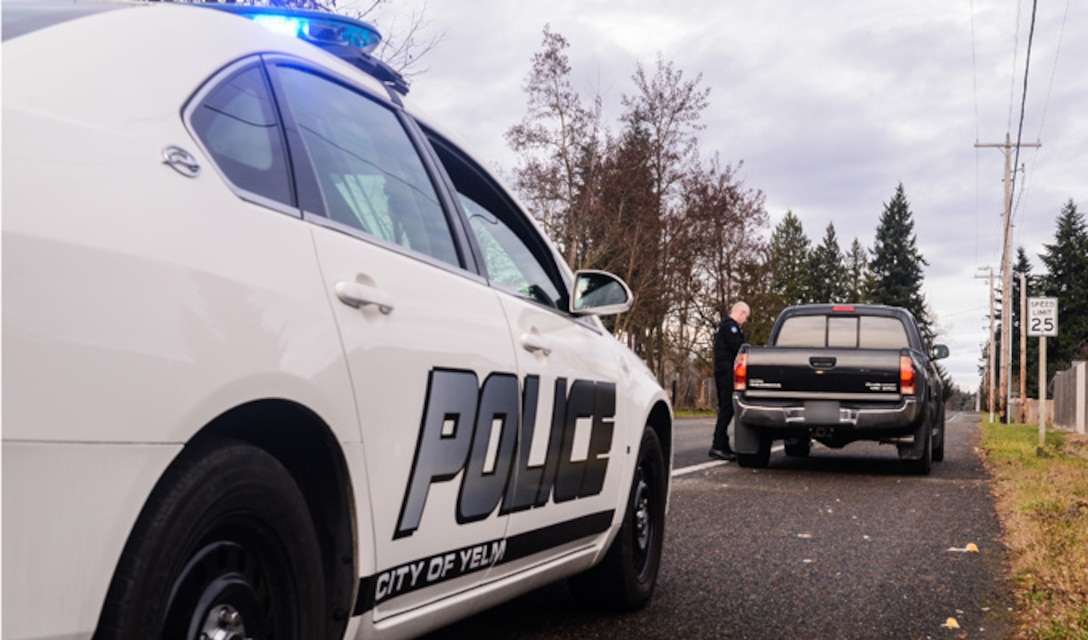 Master Sgt. Phil Ryan, collects a driver's information following a traffic stop, Dec. 14, 2013, in Yelm, Wash. Ryan is the 62nd Airlift Wing Inspector General complaint resolution superintendent, also a reserve police officer at the Yelm Police Department As a sworn peace officer, Ryan volunteers his free time with police department. (U.S. Air Force photo/Tech. Sgt. Sean Tobin)