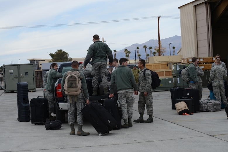 Airmen from the 366th Fighter Wing load luggage onto a truck Jan. 23, 2013, at Nellis Air Force Base, Nev. The Airmen are stationed at Mountain Home Air Force Base, Idaho, and are here participating in Red Flag 14-1. (U.S. Air Force photo by Senior Airman Benjamin Sutton/Released)
