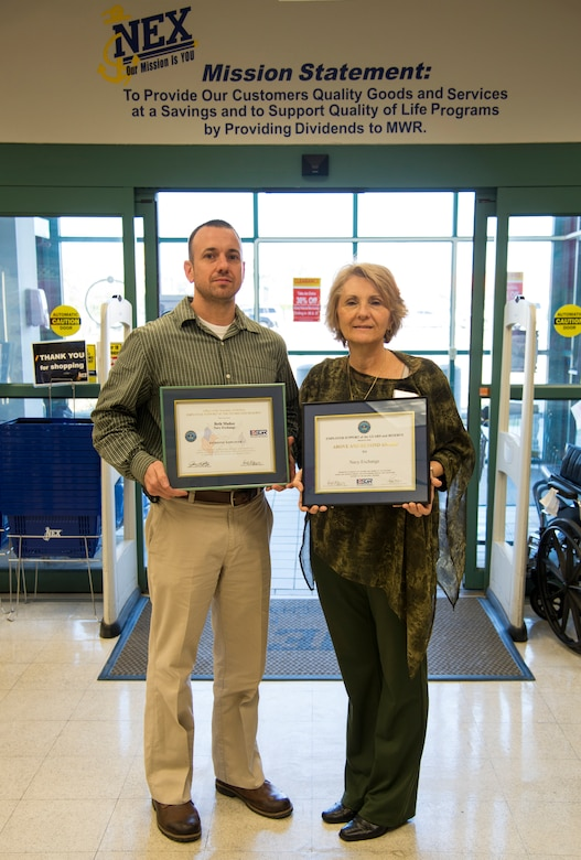 Beth Munoz, Joint Base Charleston – Weapons Station Navy Exchange general manager, stands with Alex Schmidt, NEX loss prevention manager, as they display Munoz's Patriotic Employer and Above and Beyond Awards from Employer Support of the Guard and Reserve Jan. 22, 2014, at the NEX on the Weapons Station. (U.S. Air Force photo by Airman 1st Class Clayton Cupit)