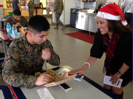 Rosalie Asuncion-Starr, Okinawa Enlisted Spouses Club president, surprises a U.S. Marine with a free gift card on Camp Foster, Japan, Dec. 19, 2013. The OESC donated $1,600 in cash and gift cards at installations throughout the island, paying for groceries, haircuts and meals to support active duty service members and their spouses. (Courtesy photo)