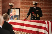 Lt. Cmdr. Raynard Allen, Navy chaplain for Headquarters and Service Battalion, Marine Corps Recruit Depot Parris Island, places a poppy on the casket of Medal of Honor recipient John James McGinty III during his funeral Jan. 23, 2014, at Beaufort National Cemetery in Beaufort, S.C. McGinty, a decorated Vietnam War hero and Parris Island veteran, died Jan. 17, 2014, in his home in Beaufort at the age of 73.