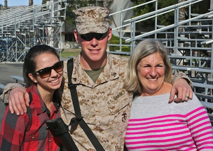 Corporal Dylan Cook, a 21-year-old ammunition technician with Ammunition Company, 1st Supply Battalion, Combat Logistics Regiment 15, 1st Marine Logistics Group, poses for the camera with his wife, Julie, and mother, Dara, before leaving on a seven-month deployment to Afghanistan in support of Operation Enduring Freedom, Jan. 19, 2014. Cook is deploying with Combat Logistics Battalion 7, along with elements of 1st Explosive Ordnance Disposal Company, 1st Medical Battalion, 1st Dental Battalion and 7th Engineer Support Battalion, to support I Marine Expeditionary Force (Fwd) in assuming responsibilities as the logistics battalion for Regional Command (Southwest).
