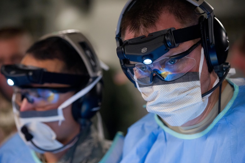 Lt. Col. Gerald Fortuna (right) performs a simulated exploratory laparotomy surgery while in flight aboard a C-17 Globemaster III during a field exercise Jan. 17, 2014, at the Joint Readiness Training Center, Fort Polk, La. Service members at JRTC 14-03 are educated in combat patient care and aeromedical evacuation in a simulated combat environment. Fortuna is a trauma surgeon with the 86th Medical Group at Ramstein Air Base, Germany. (U.S. Air Force photo/Tech. Sgt. Matthew Smith)