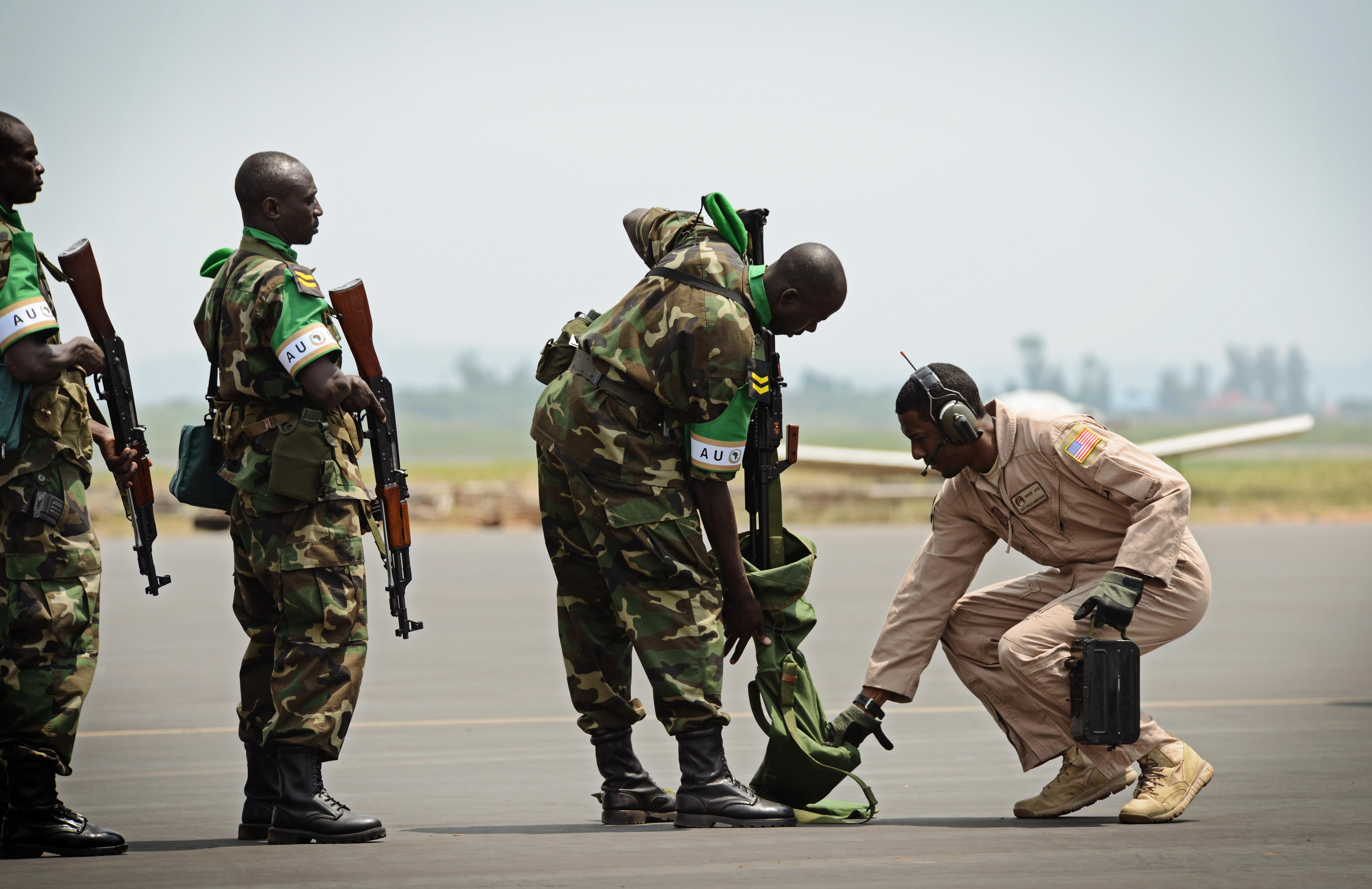 Rwandan soldiers wait in line to have their weapons inspected by Staff Sgt. Curtis McWoodson