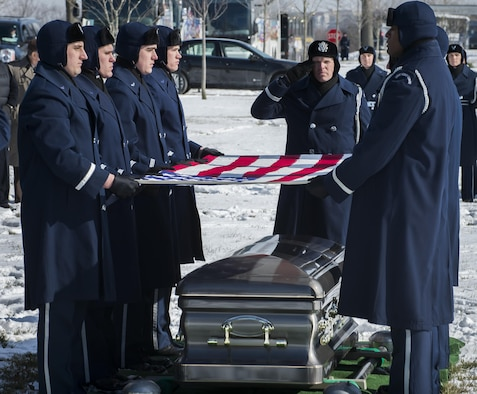 """Pall Bearers from the U.S. Air Force Honor Guard fold the flag which draped the the casket of Brig. Gen. Robinson """"Robbie"""" Risner during his internment ceremony at Arlington National Cemetery, Arlington, Va., Jan. 23, 2014. Risner was the Air Force's 20th Ace and and survived  seven and a half years of captivity as a Prisoner of War (POW) in Hoa Lo Prison, a.k.a the Hanoi Hilton. during the Vietnam War. (U.S. Air Force photo/Jim Varhegyi)"""
