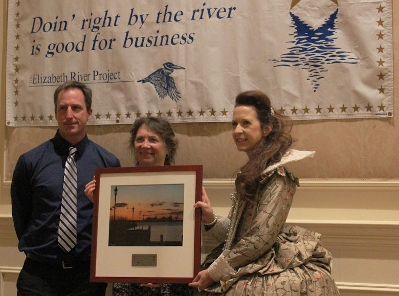 VIRGINIA BEACH, Va. -- Princess Elizabeth presents a plaque to Karin Dridge (right) and Jeff Swallow, geologists from the Norfolk District, at the annual River Stars ceremony here Jan. 23. The district was one of 109 local businesses recognized by the environmental organization for contributions in reducing pollution in the Elizabeth River by 311 million pounds since the Elizabeth River Project began in 1997. The district partnered with a local school and organizations to build a 623-square-foot sanctuary oyster reef in the Elizabeth River – a tidal estuary off the shoreline of historic Fort Norfolk, Va.