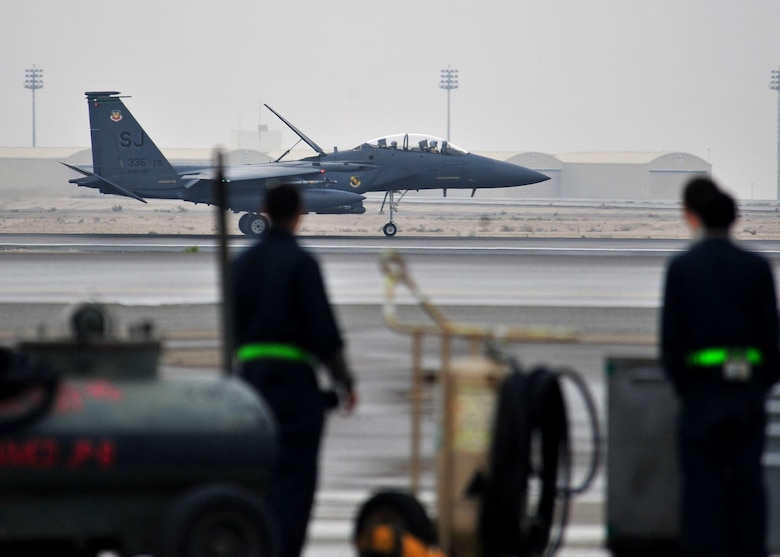 Two Airmen from the 380th Expeditionary Maintenance Group watch as an F-15E Strike Eagle lands at an airfield in Southwest Asia. The F-15E is a dual-role fighter designed to perform air-to-air and air-to-ground missions. With an array of advanced avionics and electronics systems, pilots can fight at low altitude, day or night, and in all weather. (U.S. Air Force photo/Staff Sgt. Michael Means)