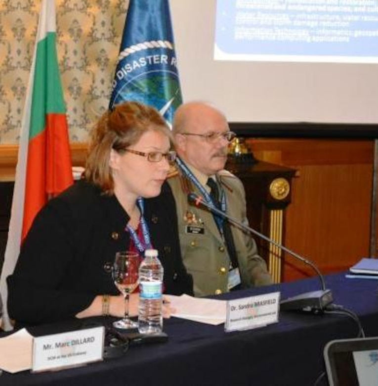 Col. Mitko Stoykov, director of NATO Crisis Management and Disaster Response Centre of Excellence, right, directed the question and answer session for EL's Dr. Sandra Brasfield at the Dec. 11 technology demonstration for the European Command (EUCOM) and EUCOM Defense Environmental International Cooperation program conference in Sofia, Bulgaria.