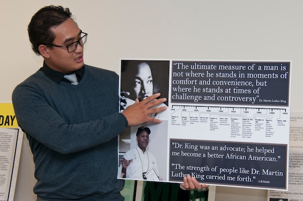 Joseph Aguila, district Equal Employment Opportunity Specialist, presents A.R. Smith with a photo collage in thanks for speaking at the Dr. King commemorative event Jan. 22.