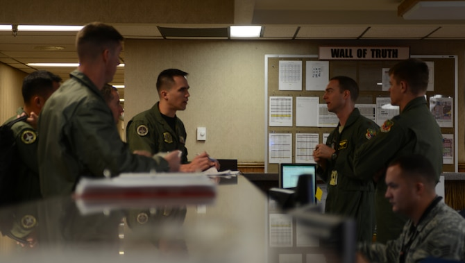 Maj. Bill Lulay, 366th Fighter Wing command post chief, speaks with aircrew personnel before their sortie Jan. 24, 2013, at Nellis Air Force Base, Nev. Aircrew from across the globe have converged at Nellis AFB to participate in the combat exercise Red Flag 14-1. (U.S. Air Force photo by Senior Airman Benjamin Sutton/Released)