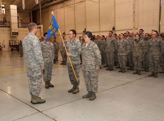 U.S. Air Force Col. Quincy N. Huneycutt, newly appointed vice commander of the 145th Airlift Wing, relinquishes command of the 145th Mission Support Group by handing the group guidon to Col. Roger E. Williams, Jr., commander 145th AW, during a Change of Command ceremony held at the North Carolina Air National Guard base, Charlotte-Douglas Intl. airport, Jan. 11, 2014. The traditional handing over of the guidon signifies the relief and acceptance of duty between two individuals from the base commander. It also allows for the accepting commander to be welcomed by their troops, as well as the departing commander to give their 'thank you' and farewell. (U.S. Air National Guard photo by Master Sgt. Patricia F. Moran/Released)