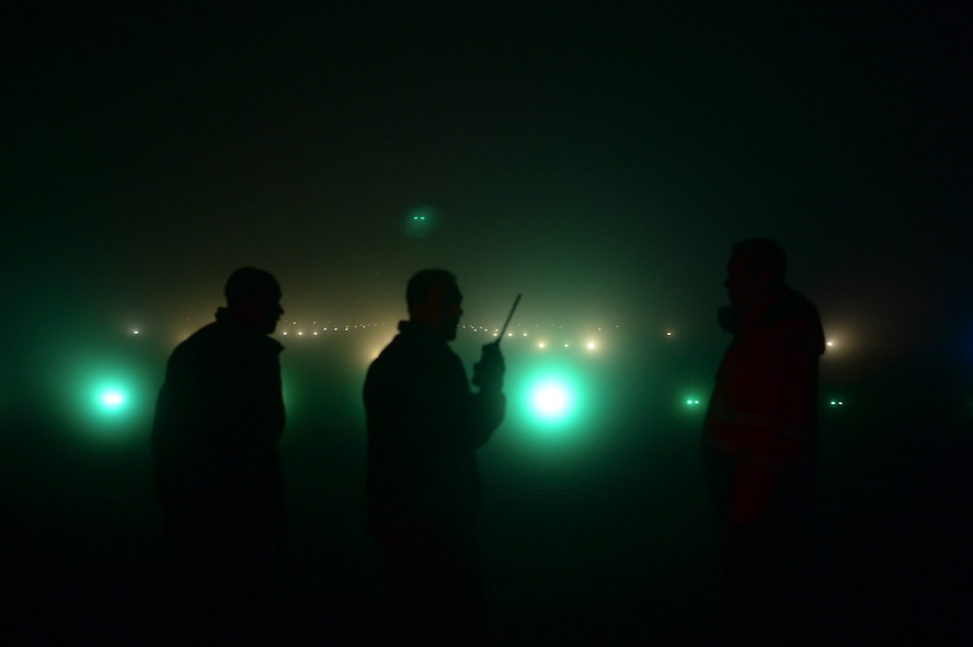 Members of the 52nd Civil Engineer Squadron observe as lights activate during a check of the airfield lighting system at Spangdahlem Air Base, Germany, Jan. 23, 2014. Members of the 52nd CES's airfield lighting check more than 3,000 lights on the airfield every day. (U.S. Air Force photo by Senior Airman Rusty Frank / Released)