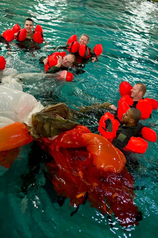 Airmen from the 133rd Operations Group take turns going underneath a parachute to simulate being entangled during water survival training at Foss Swim School in Eden Prairie, Minn., Jan 24, 2014. Water survival training encompasses equipment familiarization and processes in the event of an emergency over-water ditching scenario. (U.S. Air National Guard photo by Staff Sgt. Austen Adriaens/Released)