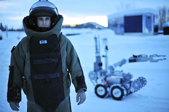 Staff Sgt. Joseph Riemer stands by an F6A robot in an explosive ordnance disposal bomb suit Jan. 21, 2014, at Eielson Air Force Base, Alaska.  Reimer works as an EOD disposal technician with the 354th Civil Engineer Squadron. (U.S. Air Force photo/Staff Sgt. Jim Araos)