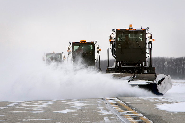 John Smith, Garth McClain and Moe Morgan, civilian contractors, remove snow from the runway at Grissom Air Reserve Base, Ind., Jan. 25, 2014, using multipurpose sweepers. After historic January snowfalls, civilian contractors have had to work hard to clear snow from Grissom's flightline so aircraft could continue to take off. (U.S. Air Force photo/Staff Sgt. Andrew McLaughlin)