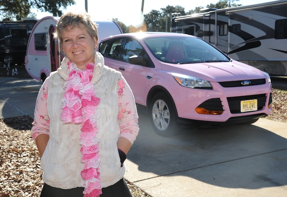 Alison Miller, widow of retired Master Sgt. Chuck Dearing, stands in front of her pink painted vehicle and teardrop trailer during a travel break Jan. 16, 2014, at the Keesler Air Force Base camp site, Biloxi, Miss. Following Dearing's retirement, the couple sold their home and belongings and traveled the country for four years staying primarily in base lodgings. Prior to the death of her husband, Miller told him that her intent was to continue traveling in a pink painted car so that he could find her while out on the road.  (U.S. Air Force photo by Kemberly Groue)