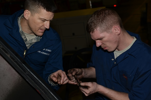 """U.S. Air Force Senior Airman Jason Brown, right, 100th Logistics Readiness Squadron vehicle maintenance journeyman from Akron, Ohio, and U.S. Air Force Chief Master Sgt. Tracy Jones, 100th Air Refueling Wing command chief, check a fire truck's dipstick Jan. 23, 2014, on RAF Mildenhall, England. Brown and Jones repeatedly checked the oil level in the fire truck to ensure it wasn't over-filled. Brown showed Jones how to perform routine maintenance as part of the """"Dirty Jobs"""" program. (U.S. Air Force photo by Airman 1st Class Preston Webb/Released)"""