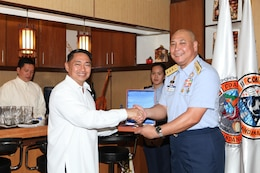 Vice Adm. Rodolfo D. Isorena (right), the Philippine Coast Guard commandant, presents a plaque to Sec. Cesar P. Garcia Jr., national security advisor to the president of the Philippines, during the initial maritime domain awareness demonstration at the Philippine Coast Guard Headquarters in Manila, Philippines, Jan. 27.