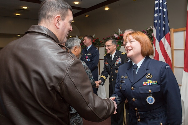 (Left to right) U.S. Air Force Col. Mark August, 374th Airlift Wing commander, congratulates Royal Australia Air Force Group Captain Barbara Courtney, United Nations Command (Rear) commander, after the UNC (Rear) change of command ceremony at Yokota Air Base, Japan, Jan. 28, 2014. As the United Nations Command's principal representative in Japan, the UNC (Rear) maintains the status of forces agreement regarding United Nations Forces in Japan during armistice conditions. (U.S. Air Force photo by Osakabe Yasuo/Released)