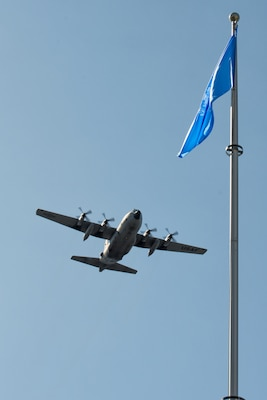 A C-130 Hercules flies over the United Nation flag at Yokota Air Base, Japan, Sept. 18, 2013. Yokota AB is one of the United Nation Command bases, under the UNC-Japan Status of Forces Agreement (SOFA) Decrees. (U.S. Air Force photo by Osakabe Yasuo/Released)