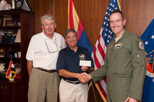 David Ray, left, Quail Creek Veterans Golf Association charitable research committee chairman, Tom Contreras, Quail Creek Veterans Golf Association president, present Col. Phil Purcell, Commander of the 162nd Fighter Wing with $1,000 check for Family Readiness Office.