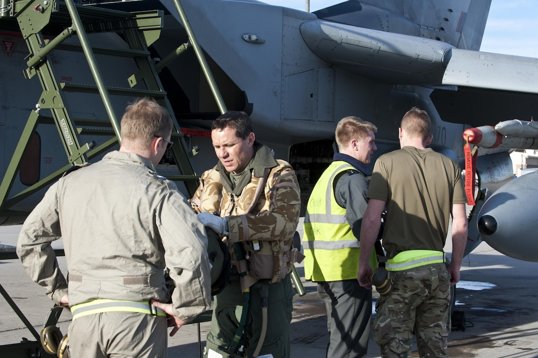 Royal Air Force Corporal Steve Pascoe talks to a pilot about a GR4 Tornado during Red Flag 14-1 Jan. 27, 2014, at Nellis Air Force Base, Nev. Red Flag gives aircrew and air support operators from various airframes, military services and allied countries an opportunity to integrate and practice combat operations. Pascoe is an IX (B) Squadron mechanical engineer from RAF Marham, United Kingdom. (U.S. Air Force photo/Senior Airman Matthew Lancaster)