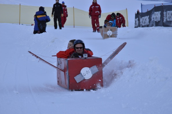 Col. David Gibson and Grant Sparkman slide down the cardboard derby race course Jan. 25 during the 24th annual SnoFest. The team from the Academy Dean of Faculty's computer science department took first place in the group category for fastest snow craft. (U.S. Air Force Photo/Patrice Clarke)