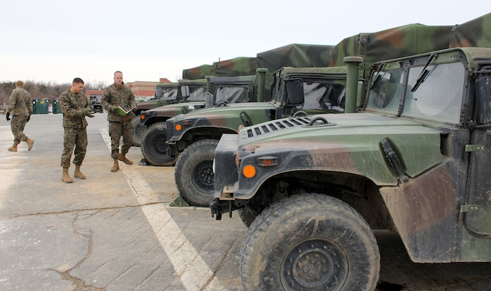 Marines with Motor Transportation Operations, The Basic School, inspect a row of Humvees on Jan. 29, 2014, aboard Marine Corps Base Quantico. Marines in motor transportation are responsible for delivering people, water, ammunition and all other resources to the front lines. The Department of Defense aims to become more sustainable through alternative energy methods that will reduce risk to forces delivering those resources.