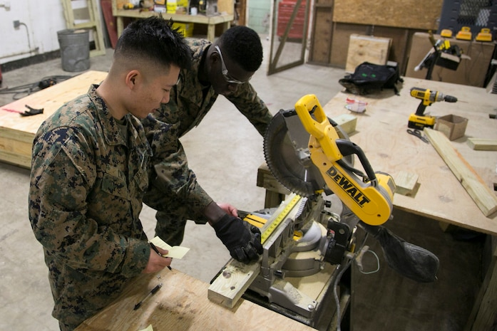 Cpl. Jun Lin, a supply shipping clerk for Marine Aviation Logistics Squadron 31, teaches Lance Cpl. Micheal Dillard, an aviation supply specialist for MALS-31, how to package shipping items at the supply warehouse aboard Marine Corps Air Station Beaufort, Jan. 28.
